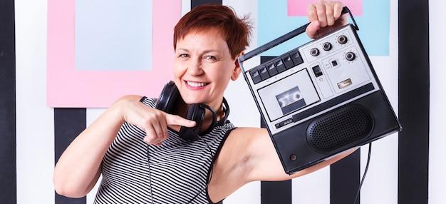 Femme senior hipster montrant un lecteur de cassettes vintage Photo gratuit