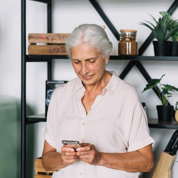 Femme senior souriante debout devant l'étagère à l'aide d'un téléphone portable Photo gratuit