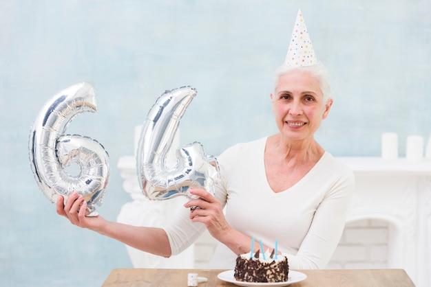 Femme senior souriante montrant un ballon en feuille de 64 numéros avec son gâteau d'anniversaire sur la table Photo gratuit
