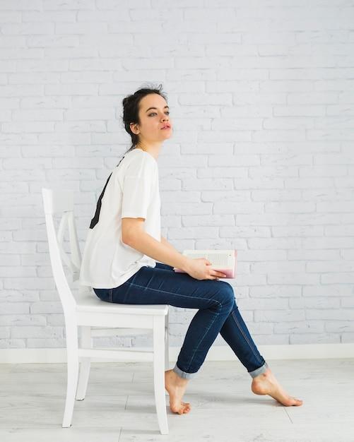Femme sensuelle avec un livre sur une chaise Photo gratuit