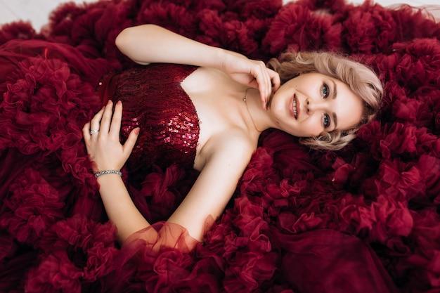 Femme sensuelle en robe burgundi rouge se trouve sur le sol dans une pièce lumineuse Photo gratuit