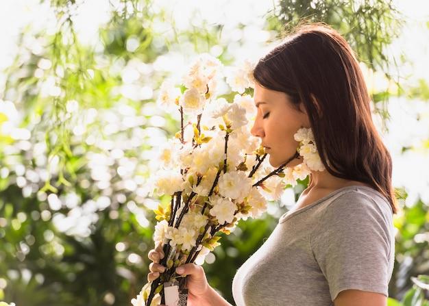 Femme sentant les fleurs blanches Photo gratuit