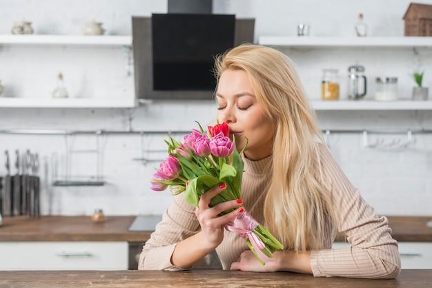 Femme, sentir, frais, fleurs, cuisine Photo gratuit