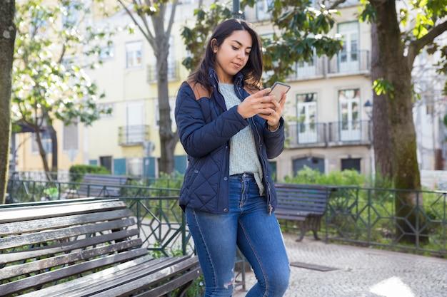 Femme Sérieuse à L'aide De Smartphone Et Debout à L'extérieur Photo gratuit