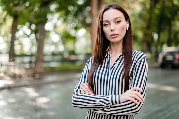 Femme sérieuse, à, oreillettes sans fil, debout, à, mains croisées, dehors Photo Premium
