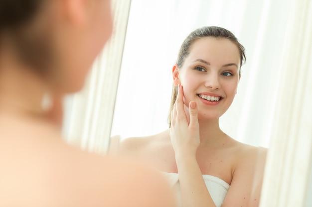 femme sortant de la douche qui se regarde un miroir