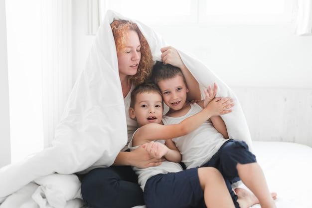 Femme et ses enfants enveloppés dans une couverture Photo gratuit