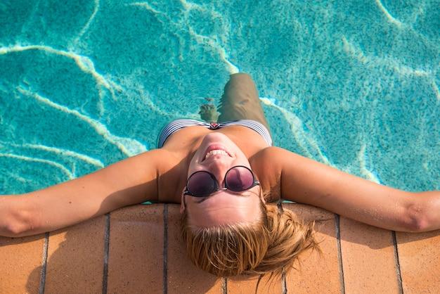 Femme Sexy En Bikini Bénéficiant Du Soleil D'été Et Du Bronzage Pendant Les Vacances En Piscine. Vue De Dessus. Femme En Piscine. Femme Sexy En Bikini. Photo gratuit