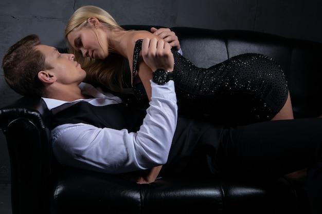 Une Femme Sexy Dans Une Robe Noire Embrasse Un Bel Homme Allongé Sur Le Canapé. Photo Premium