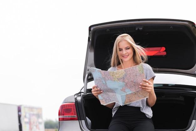 Femme sexy regardant sous le capot de la voiture Photo gratuit