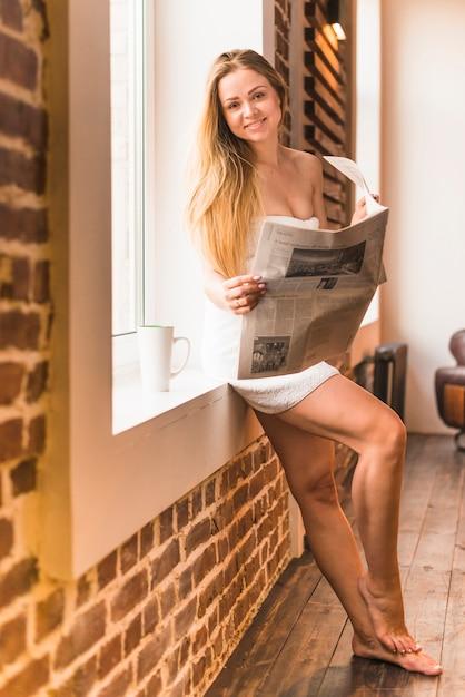 Femme sexy souriante se penchant près de fenêtre tenant le journal Photo gratuit