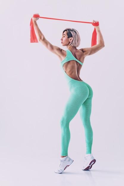 Femme Sexy En Tenue De Sport à L'aide D'une Bande De Résistance Dans Sa Routine D'exercice. Jeune Femme Effectue Des Exercices De Fitness Sur Mur Blanc. Photo Premium