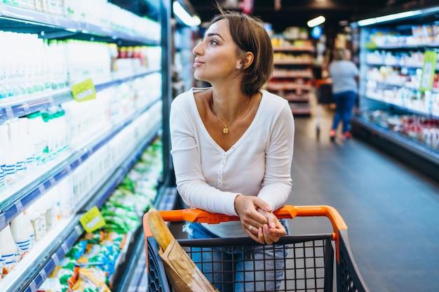 Femme shopping à l'épicerie, près du réfrigérateur Photo gratuit