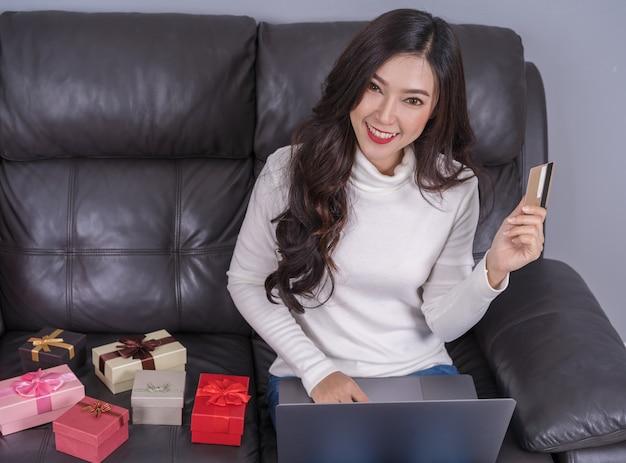 Femme shopping en ligne pour cadeau avec ordinateur portable dans le salon Photo Premium
