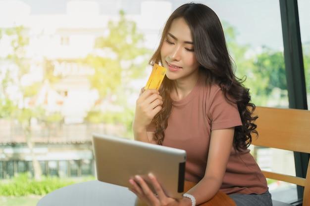 Femme shopping en ligne avec sa carte de crédit et sa tablette. Photo Premium