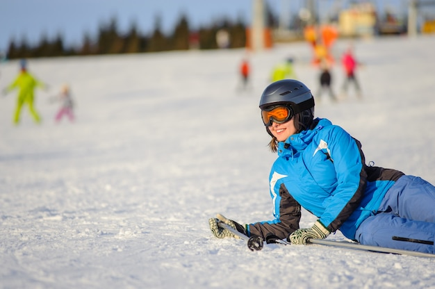 Femme de skieur allongée sur la neige à la station de ski par une journée ensoleillée Photo Premium