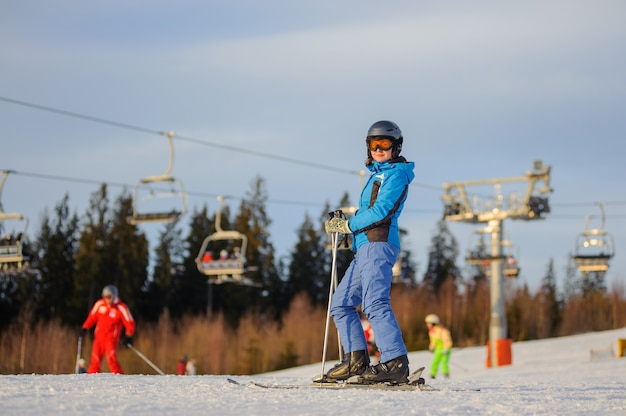 Femme skieuse contre les remontées mécaniques et la forêt par une journée ensoleillée Photo Premium