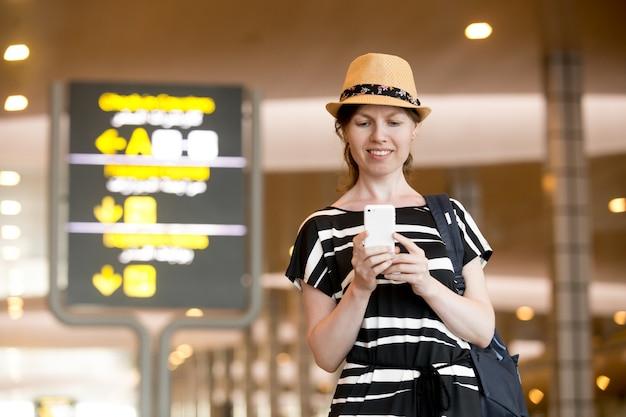 Femme avec un smartphone à l'aéroport Photo gratuit