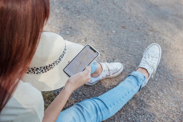 Femme Avec Smartphone S'appuyant Contre Sa Voiture Photo gratuit