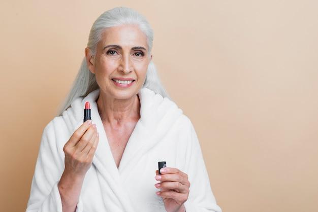 Femme smiley devant tenant le rouge à lèvres Photo gratuit