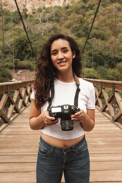 Femme smiley grand angle avec caméra sur pont Photo gratuit