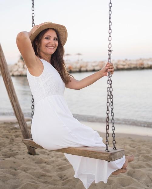 Femme Smiley Plein Coup Se Balançant à La Plage Photo Premium