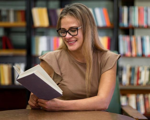 Femme Smiley Tir Moyen Lecture Photo gratuit