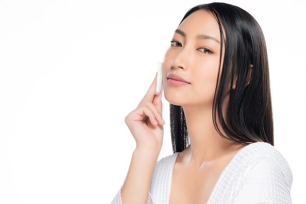 Femme de soin de peau démaquillant le visage avec un tampon de coton tige. Photo Premium