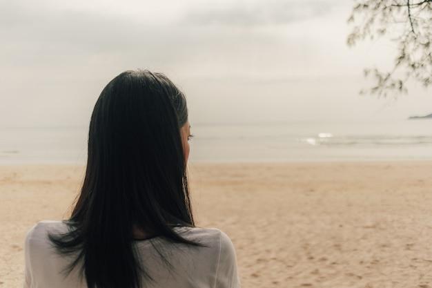 Femme Solitaire Debout Sur La Plage Et Regarde Dans La Mer. Photo Premium
