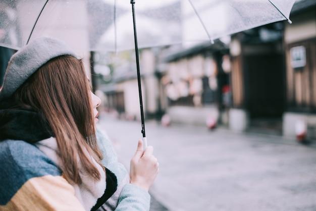 Une femme solitaire avec un parapluie attend la pluie dans la rue au japon. Photo Premium