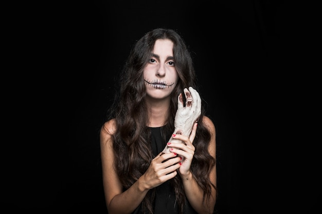 Femme sombre tenant la main morte Photo gratuit