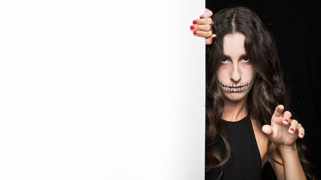 Femme sombre tenant un tableau blanc et la main levée Photo gratuit