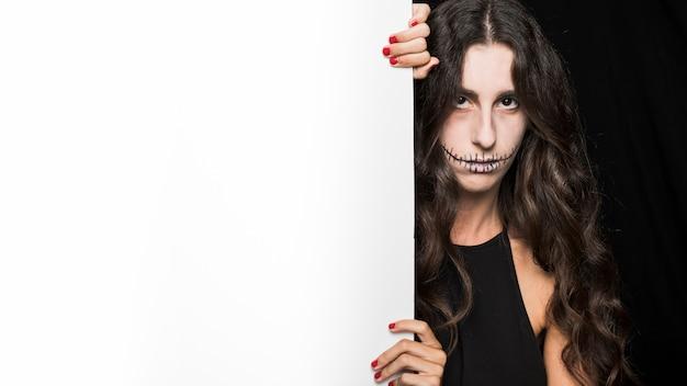 Femme sombre tenant un tableau blanc Photo gratuit