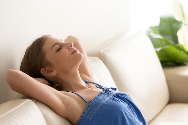Femme sommeille sur le canapé, les mains derrière la tête Photo gratuit