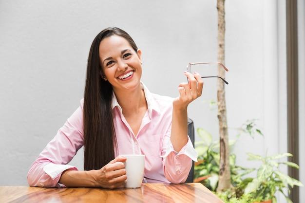 Femme à son bureau avec une tasse de café Photo gratuit