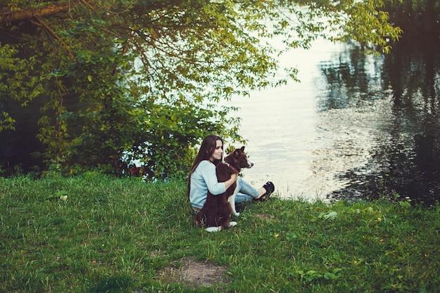 Femme et son chien assis en plein air Photo Premium