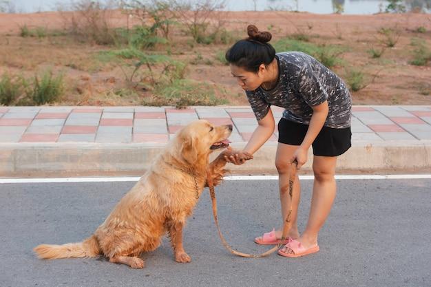 Femme avec son chien golden retriever marchant sur la voie publique. Photo Premium
