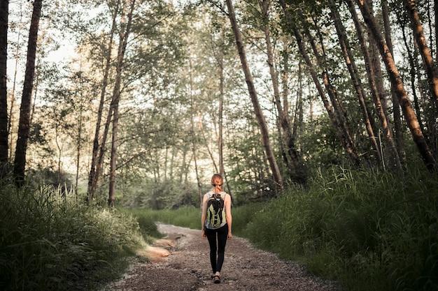 Femme avec son sac à dos de randonnée dans la forêt Photo gratuit