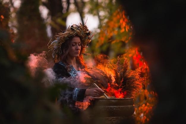 Femme sorcière fait un sort avec chaudron sur la forêt Photo Premium