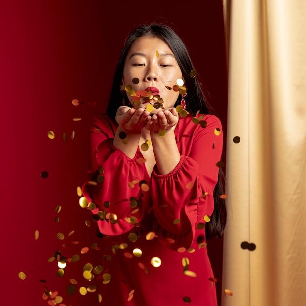 Femme soufflant des confettis dorés Photo gratuit
