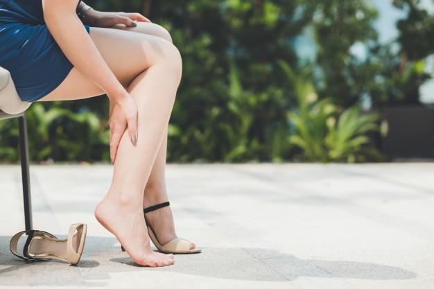La femme souffre de porter des chaussures à talons hauts Photo Premium