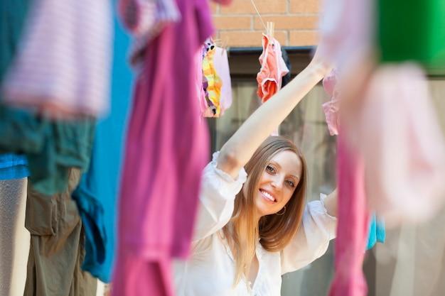 Femme Souriante Accrochant Des Vêtements Après La Lessive Photo gratuit