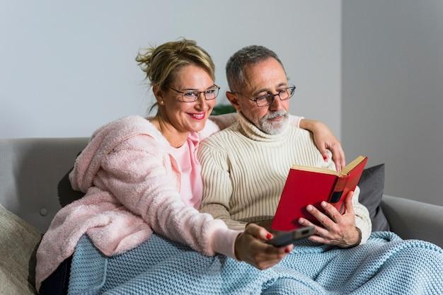 Une femme souriante âgée avec télécommande en regardant la télévision et un homme lisant un livre sur le canapé Photo gratuit