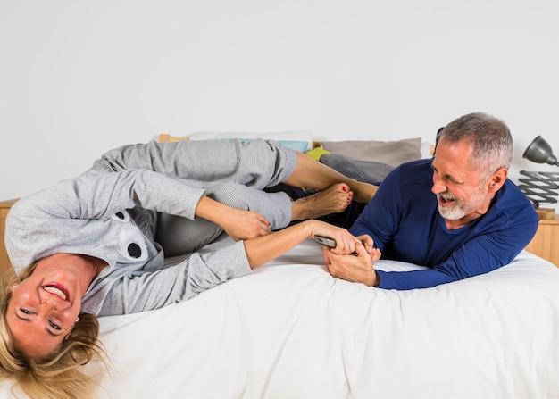 Femme souriante âgée voulant prendre la télécommande d'un homme les mains sur le lit Photo gratuit