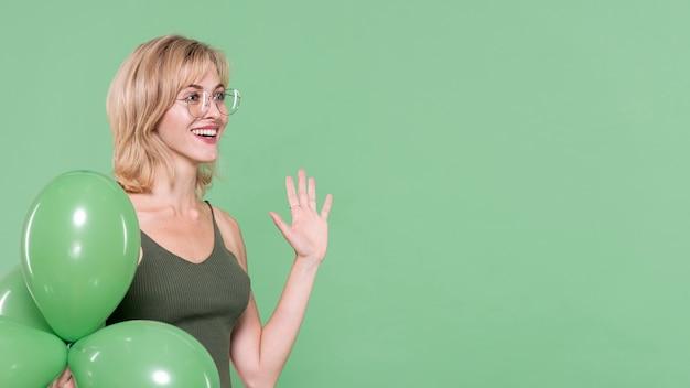 Femme souriante agitant sa main Photo gratuit