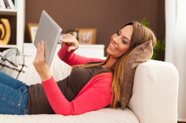 Femme Souriante Allongée Sur Le Canapé Et à L'aide De Tablette Numérique Photo gratuit
