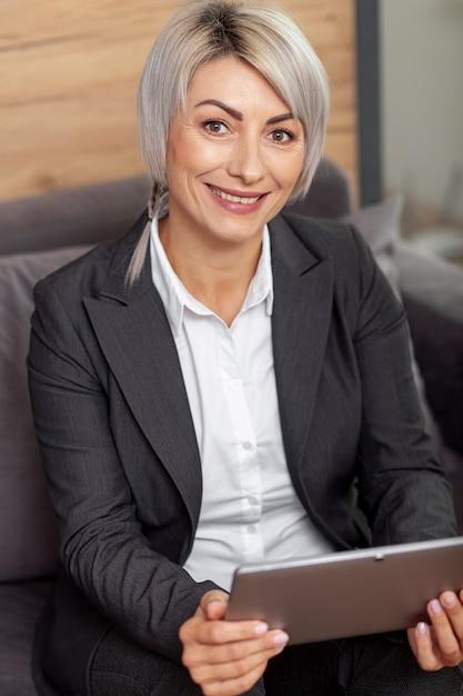 Femme souriante au bureau tenant la tablette Photo gratuit