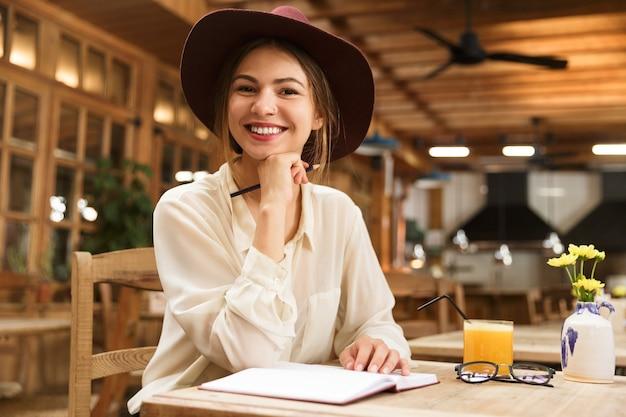 Femme Souriante Au Chapeau Assis à La Table De Café à L'intérieur Photo Premium