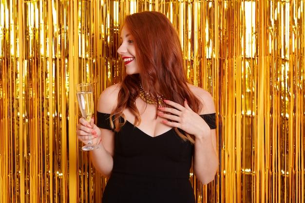 Femme Souriante Aux Cheveux Rouges Avec Verre De Vin à Côté, Vêtue D'une Robe Noire Aux épaules Nues, Se Dresse Contre Le Mur Avec Des Guirlandes D'or Photo Premium