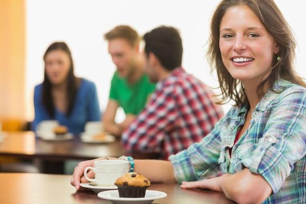 Femme Souriante Ayant Un Café Et Un Muffin Au Café Photo Premium